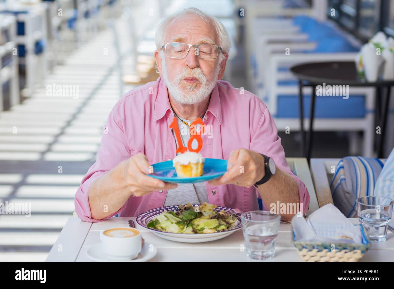 Homme d'âge positif ayant un anniversaire Photo Stock