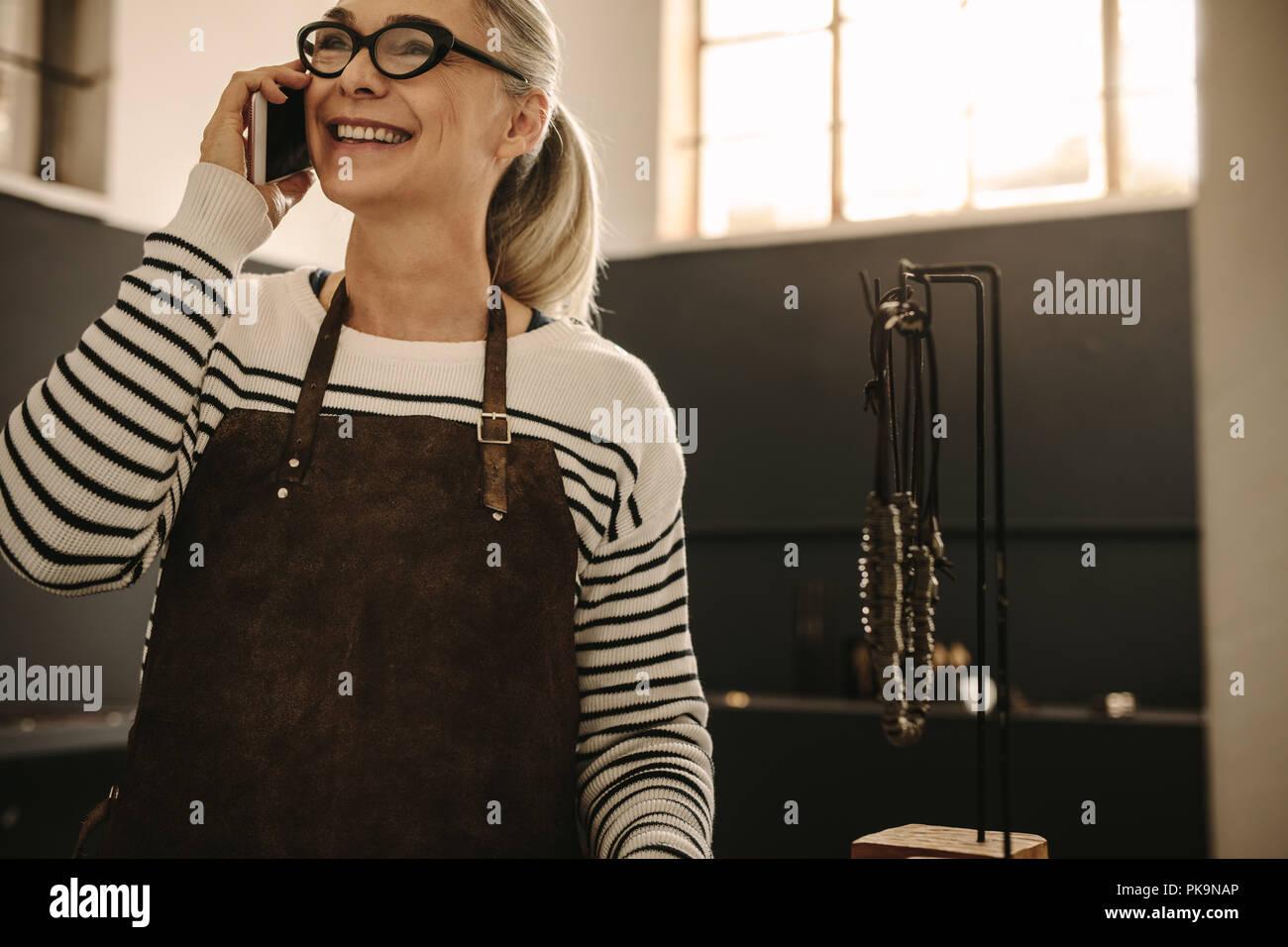 Portrait of senior woman wearing apron talking on mobile phone and smiling at atelier de bijouterie. Femme goldsmith faisant appel de sa le desi Photo Stock