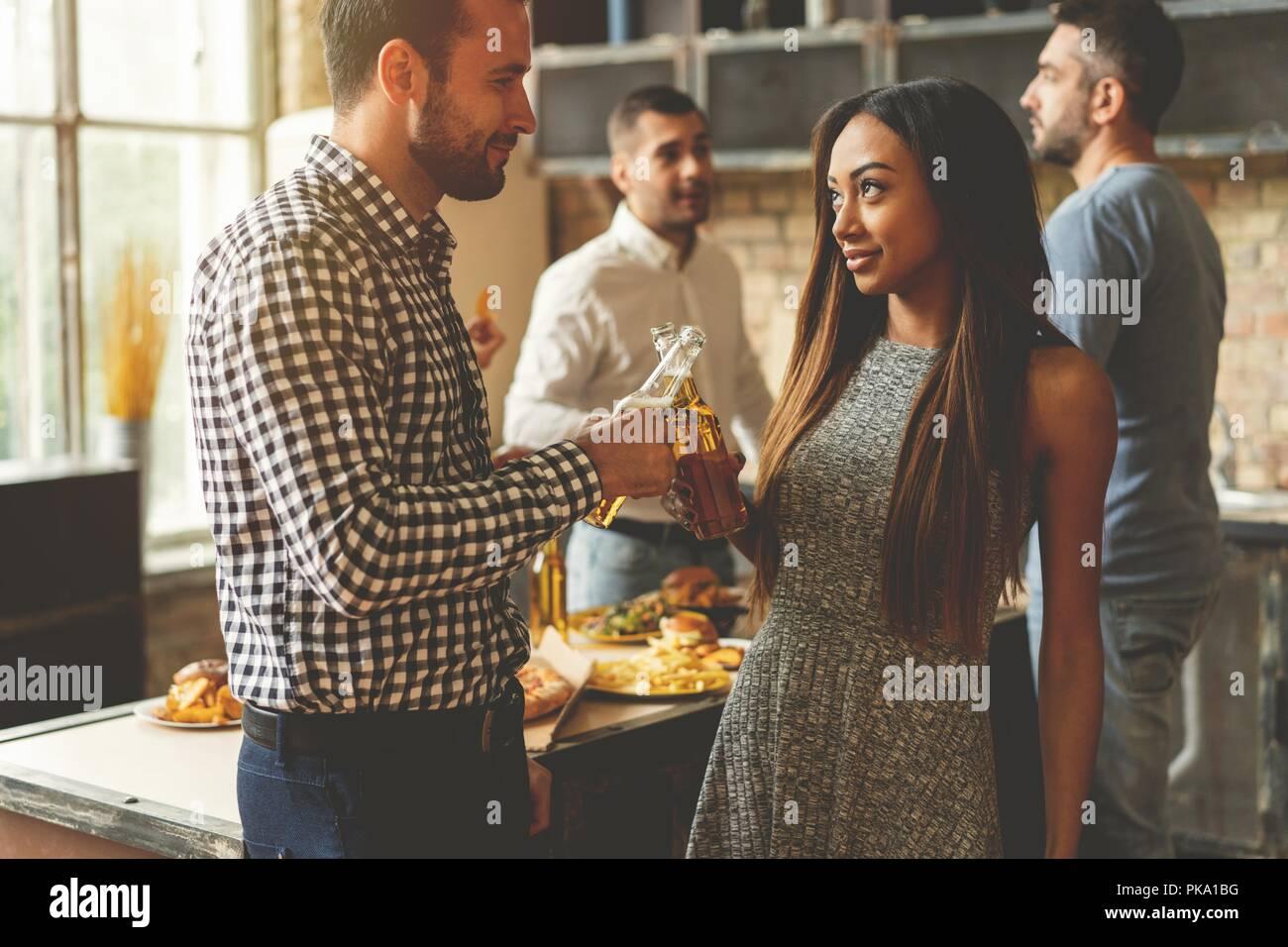 Partie avec ses meilleurs amis. Group of cheerful young people enjoying home party avec des collations et des boissons tout en communiquant sur la cuisine. Photo Stock