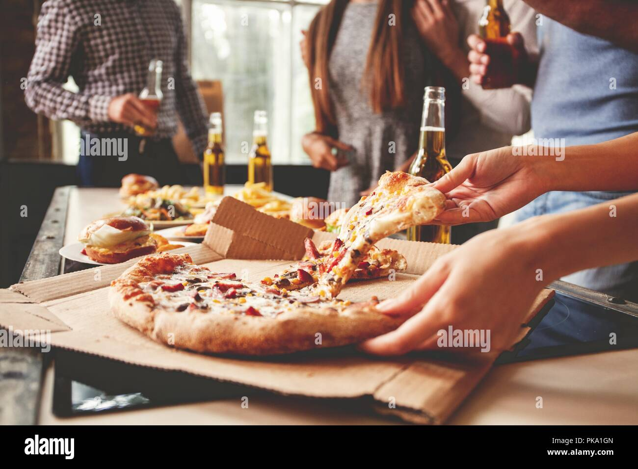 Les amis de prendre des tranches de pizza savoureuse de la plaque, vue en gros plan. Photo Stock