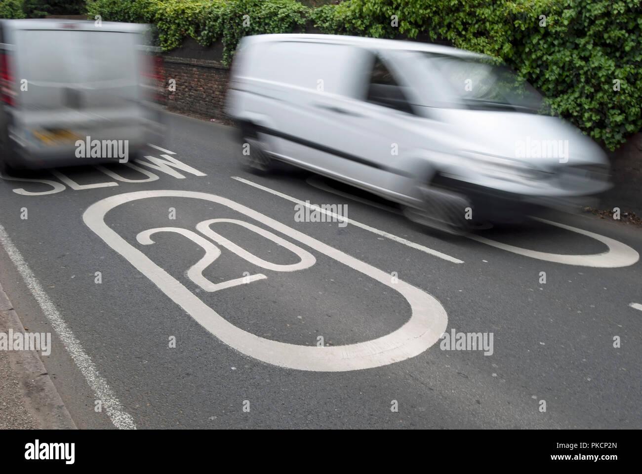 Vu les véhicules dans blurred motion note de marquage routier indiquant une limite de vitesse de 20mph à ham, Surrey, Angleterre Photo Stock