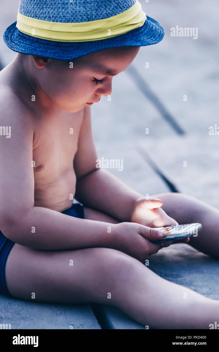 Mignon petit bébé garçon avec chapeau assis sur la plage et jouer avec smartphone. Enfant l'apprentissage de l'utilisation de smartphone. Boy texting sur le téléphone. - Techn Photo Stock