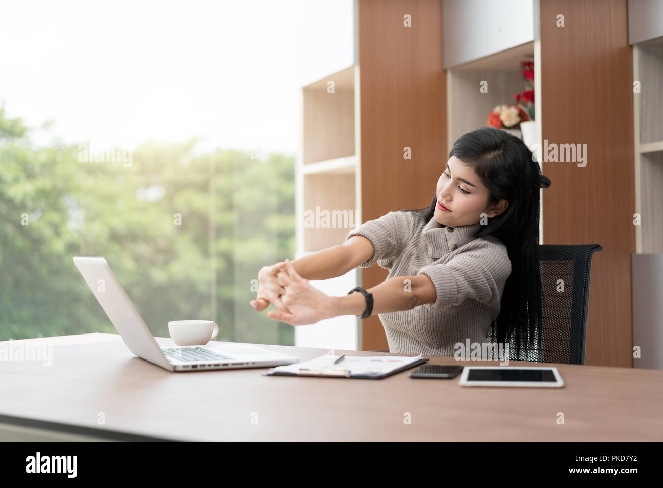 Young Asian businesswoman est relaxing in office. Asian businesswoman s'étire son corps. Banque D'Images