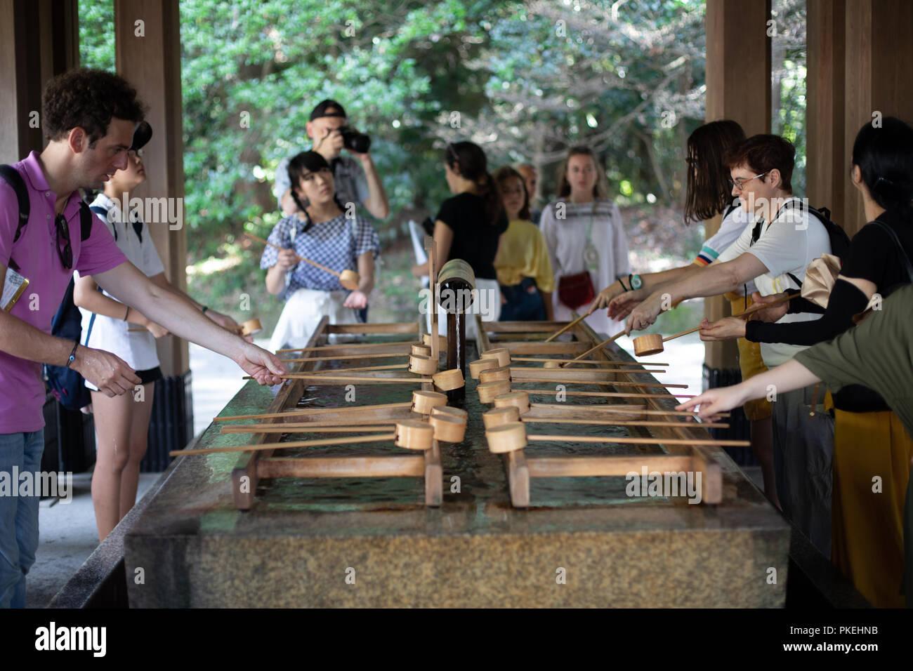Les visiteurs du sanctuaire de Meiji à Tokyo nettoyer les mains dans une procédure de purification rituelle. Photo Stock