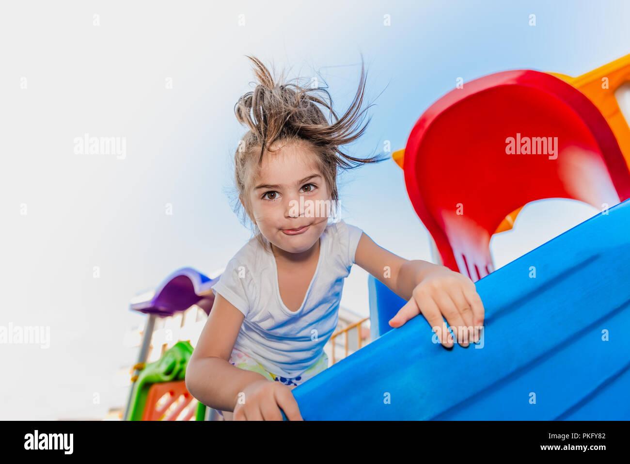 Portrait of cute little girl holding et de l'escalade pour atteindre les curseurs haut sur jeux pour enfants Photo Stock