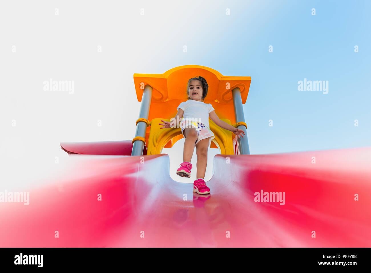 Portrait of cute little girl essayant de marcher sur glissière rose de haut en bas sur l'aire de jeux Banque D'Images