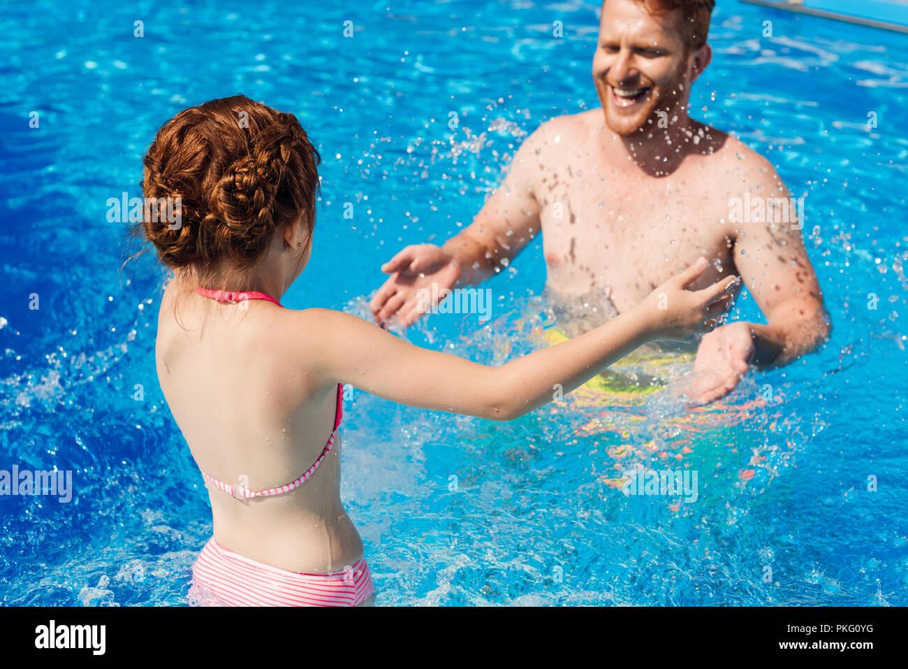 Père et fille espiègle éclaboussures avec de l'eau dans la piscine Photo Stock