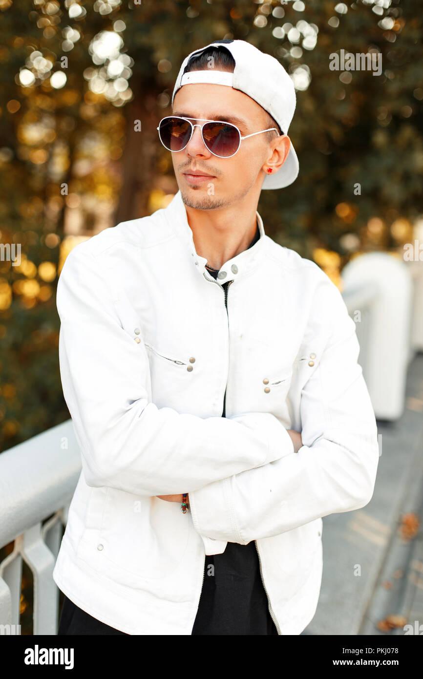 5cccd3d64518e Beau jeune homme élégant à lunettes en blanc des vêtements à la mode ...
