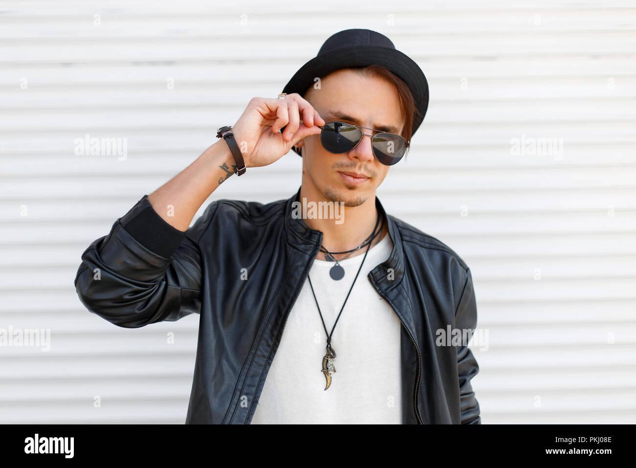 Beau jeune homme avec des lunettes de soleil dans une veste en cuir noir  avec blanc 963ceb955499
