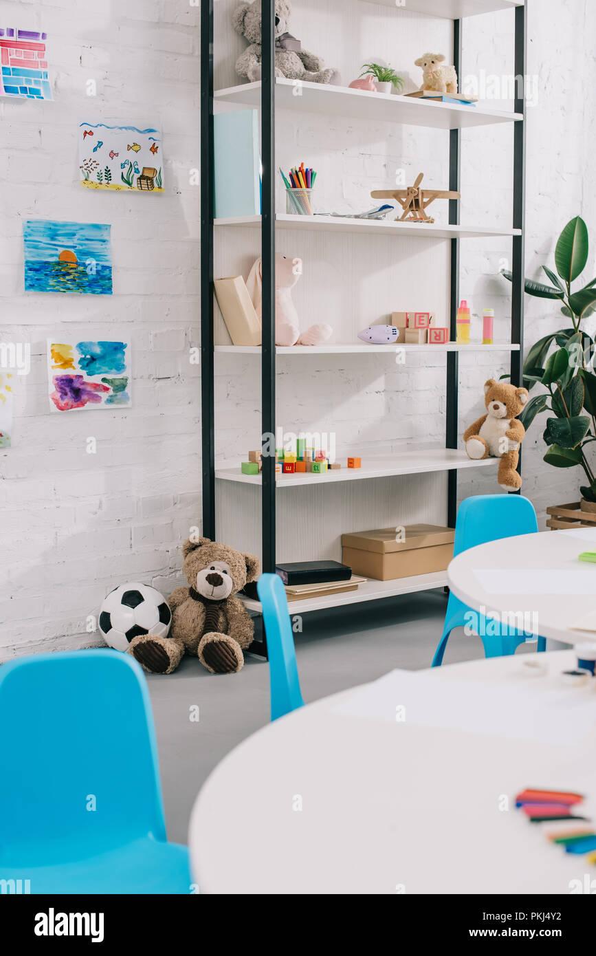 Vue en gros jouets, des dessins colorés sur le mur blanc dans la classe vide Banque D'Images