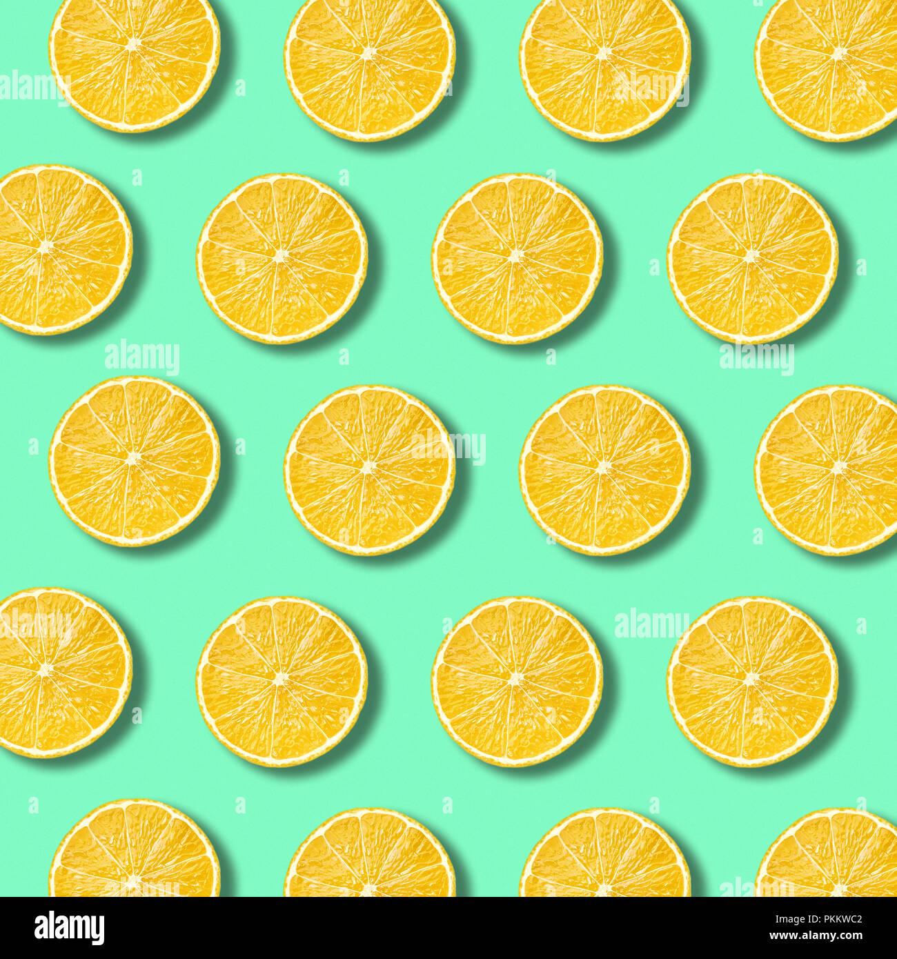 Les tranches de citron sur un fond de couleur vert éclatant de lumière. La texture des aliments non forfaitaire minime Photo Stock