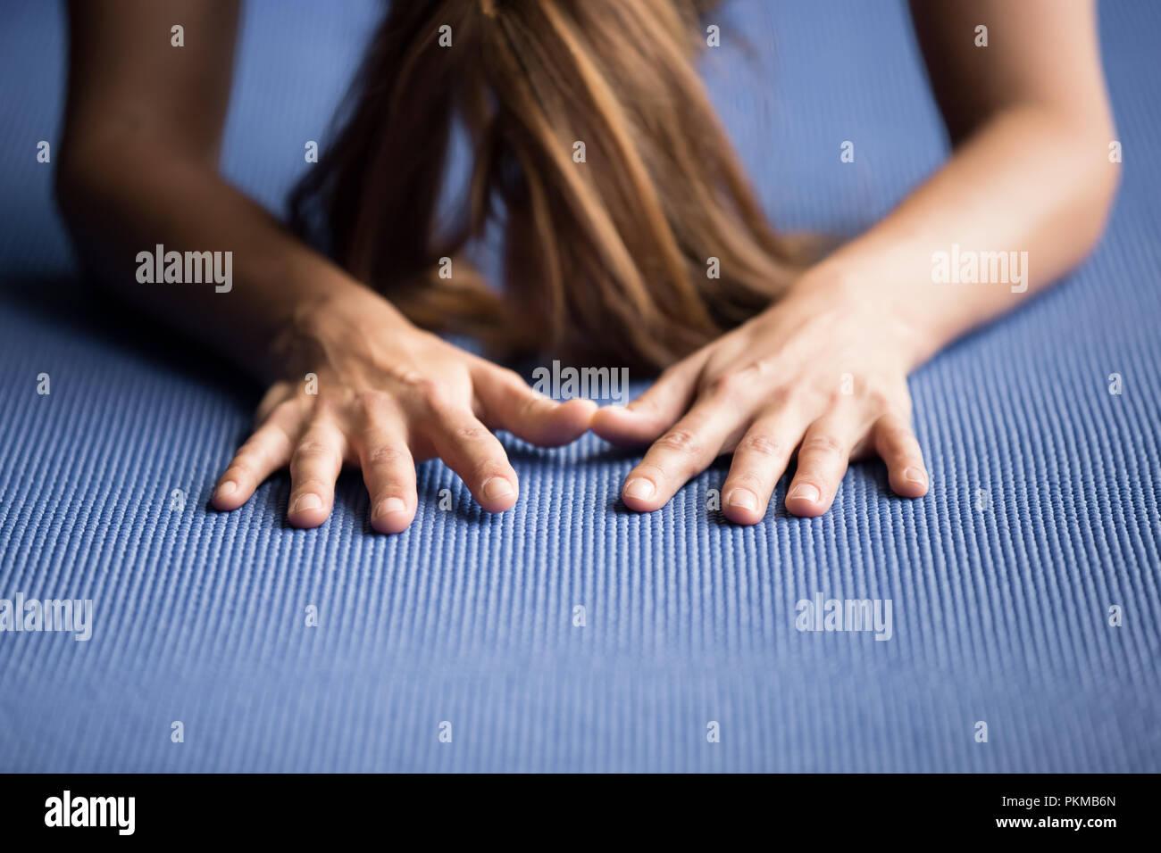 Sporty woman practicing yoga sur un tapis bleu Photo Stock