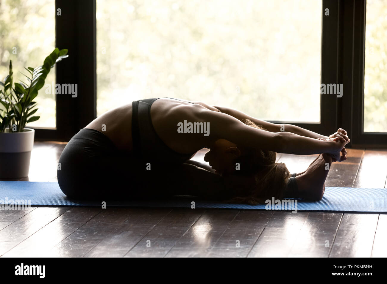 Young woman doing yoga exercice paschimottanasana Photo Stock
