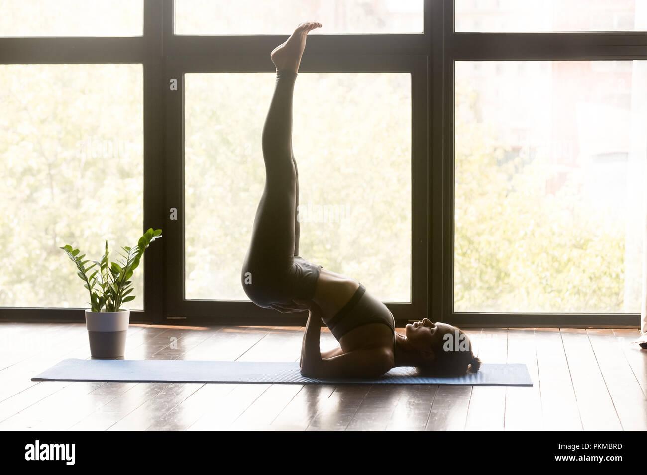 Young woman practicing yoga en Viparita Karani poser Photo Stock