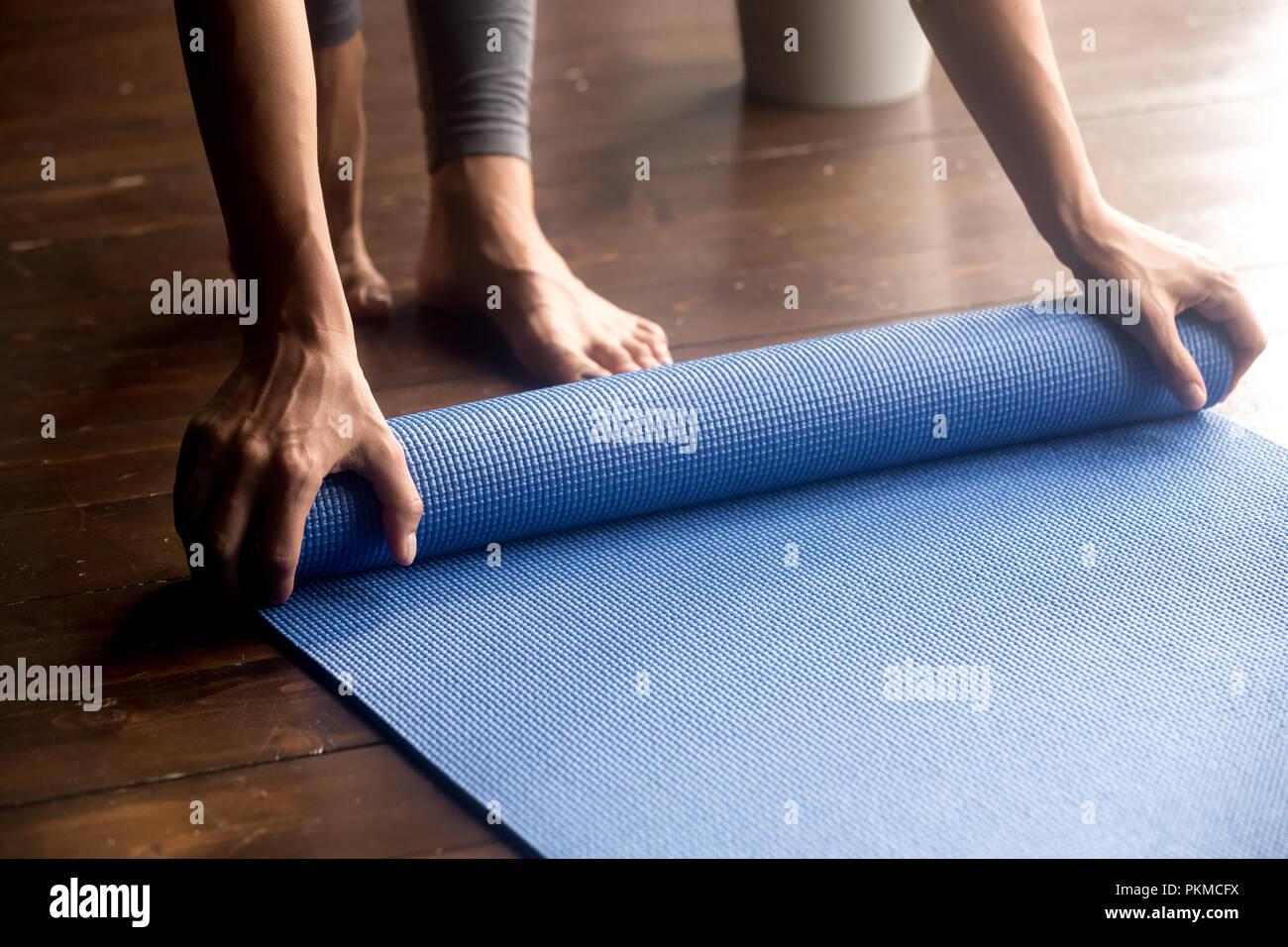 Temps pour la pratique, les mains en déroulant le tapis yoga bleu Photo Stock