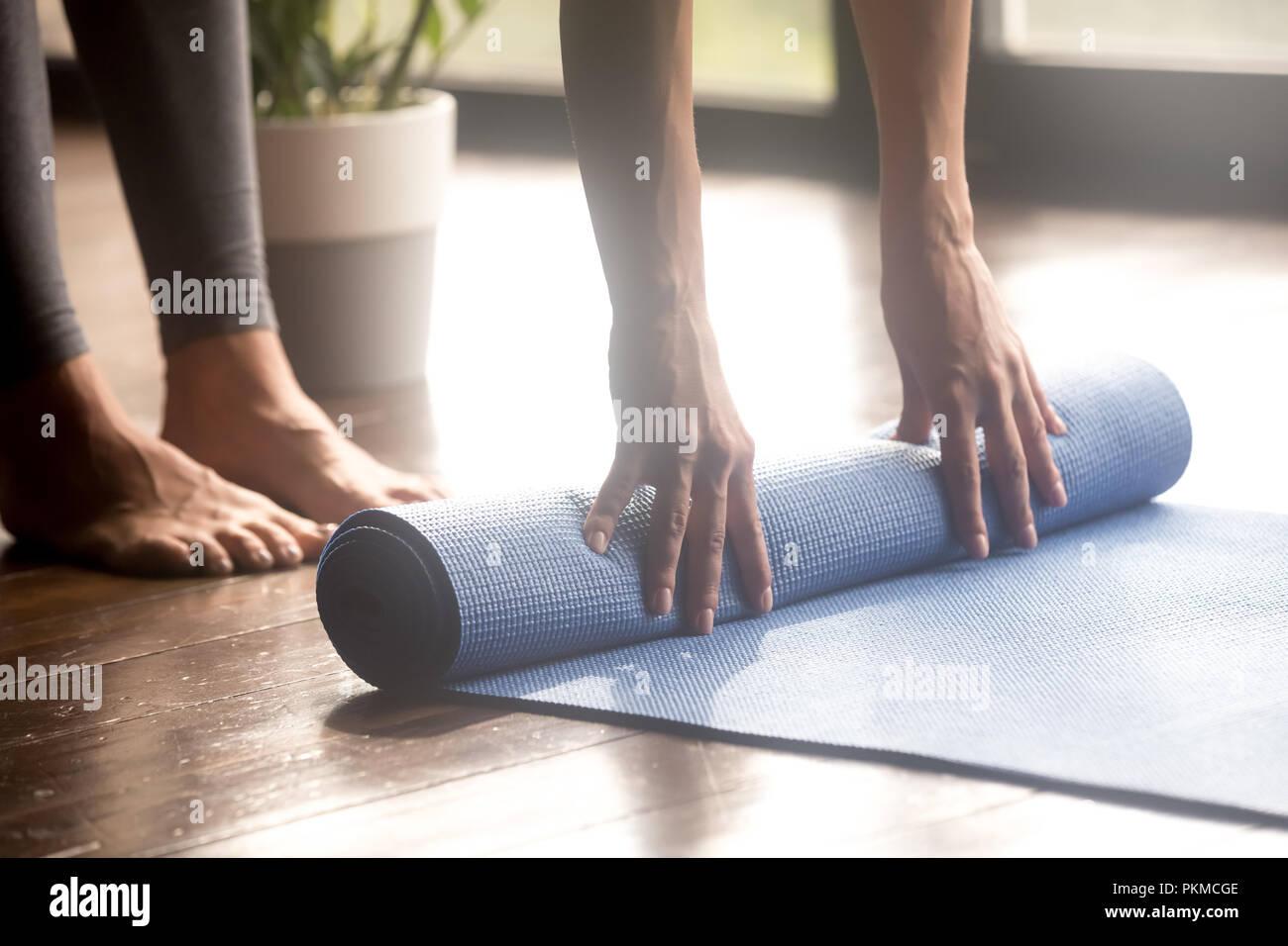 Dérouler le tapis yoga bleu femme, jambes close up Photo Stock