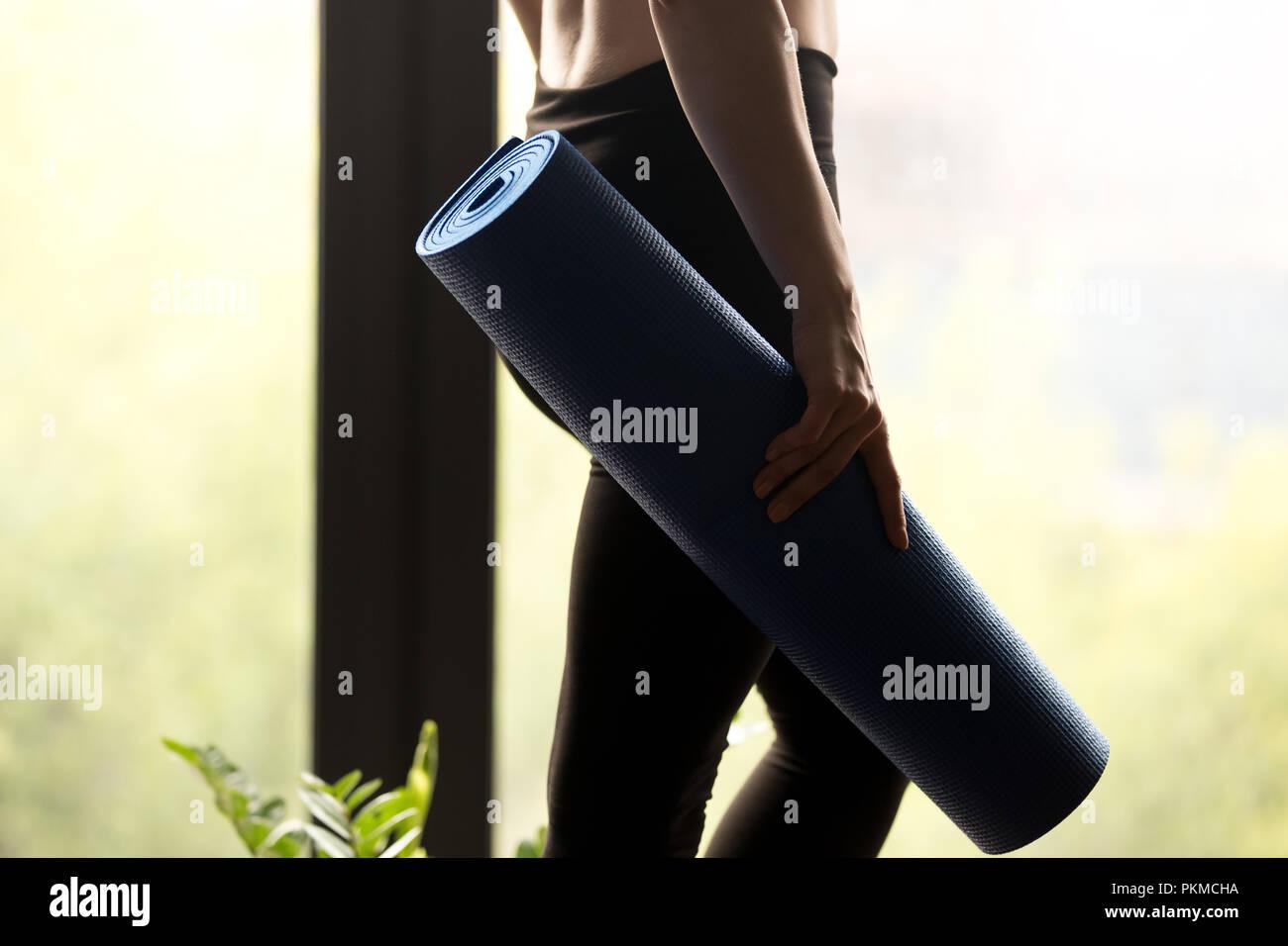 Sporty woman holding yoga mat, Close up Photo Stock