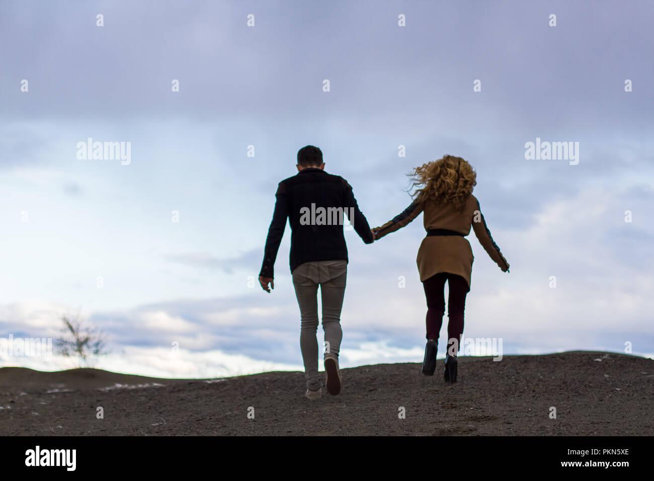 Beau couple amoureux à la Saint-Valentin. Happy young couple en train de marcher sur la plage de sable de montagne sur un jour nuageux Photo Stock