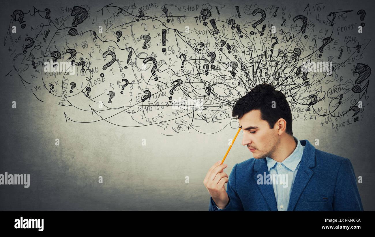 Jeune homme a souligné réfléchie avec un fouillis dans sa tête les yeux fermé pointant crayon pour le front. L'anxiété et les maux de tête sensation. Photo Stock