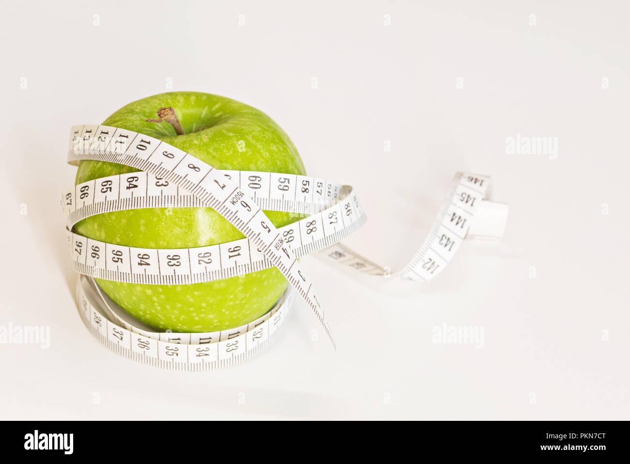 Mètre à ruban enroulé autour d'une pomme verte. Photo Stock