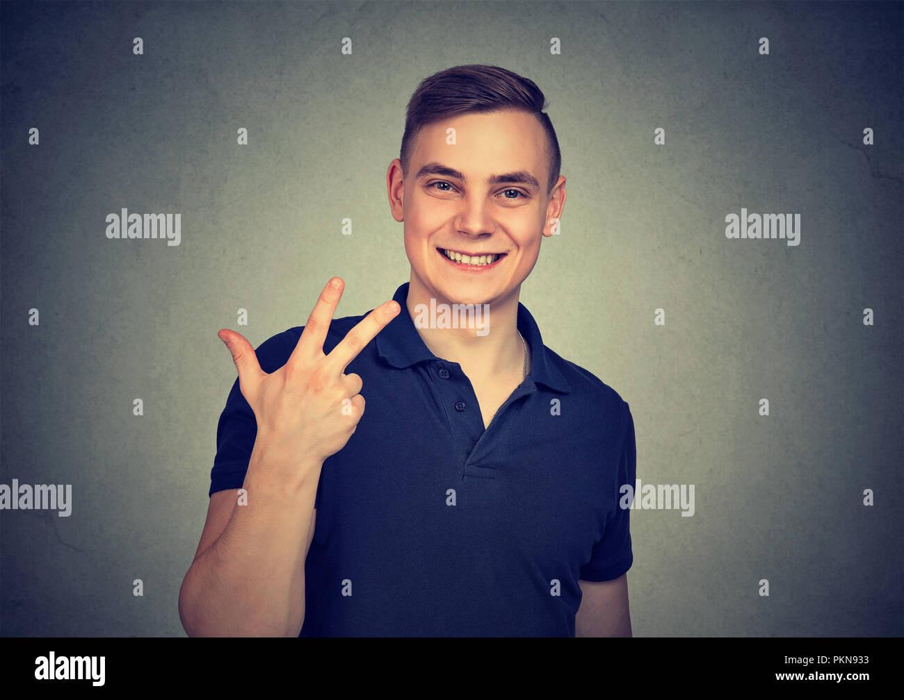 Jeune homme montrant trois doigts tout en proposant de traiter et sur fond gris Photo Stock
