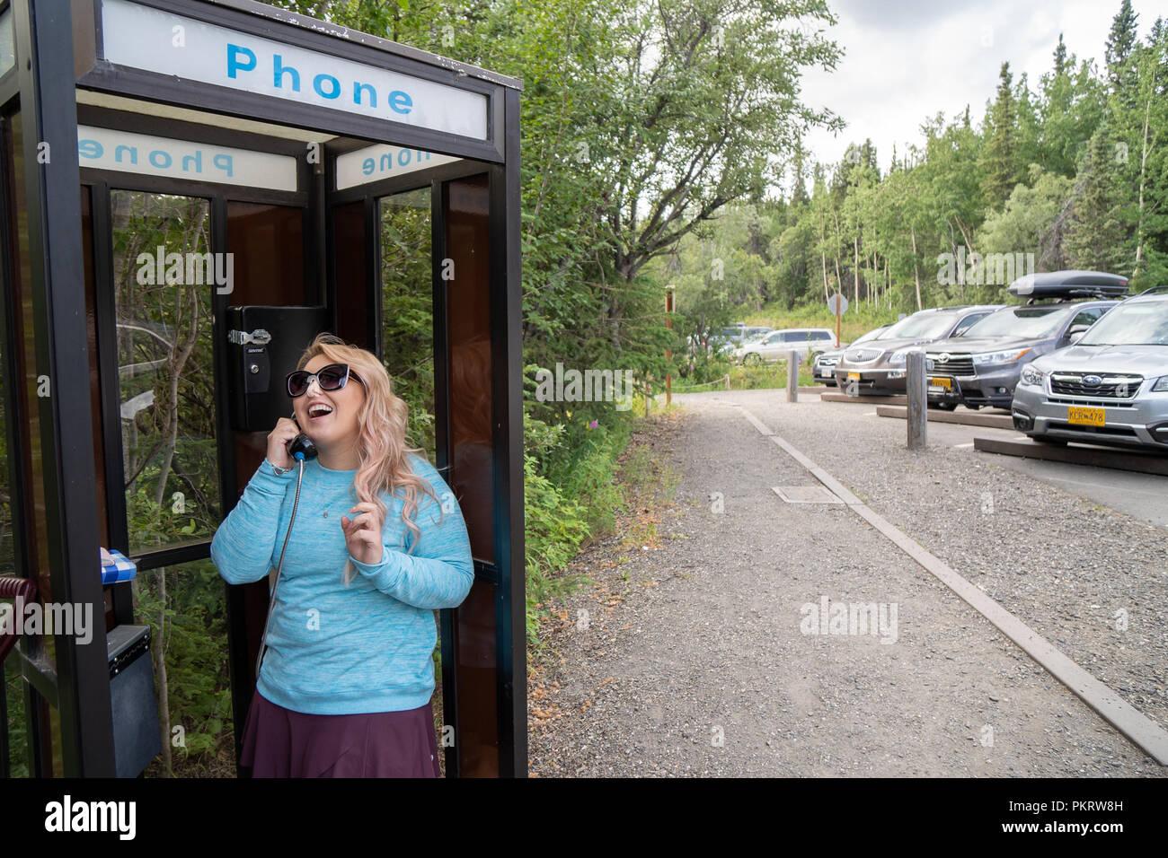 Femme blonde parle sur un téléphone fixe dans une cabine téléphonique rétro. Concept pour la technologie rétro, une technologie dépassée Photo Stock