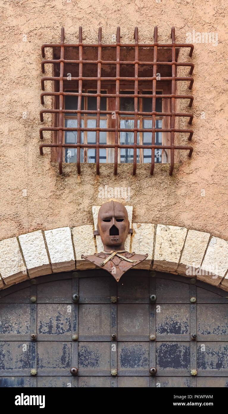 Masque de fer au-dessus d'une vieille porte dans le Suquet sur le Tour du masque, une tour qui est hanté par le fantôme de l'homme au masque de fer près du château de Ca Banque D'Images