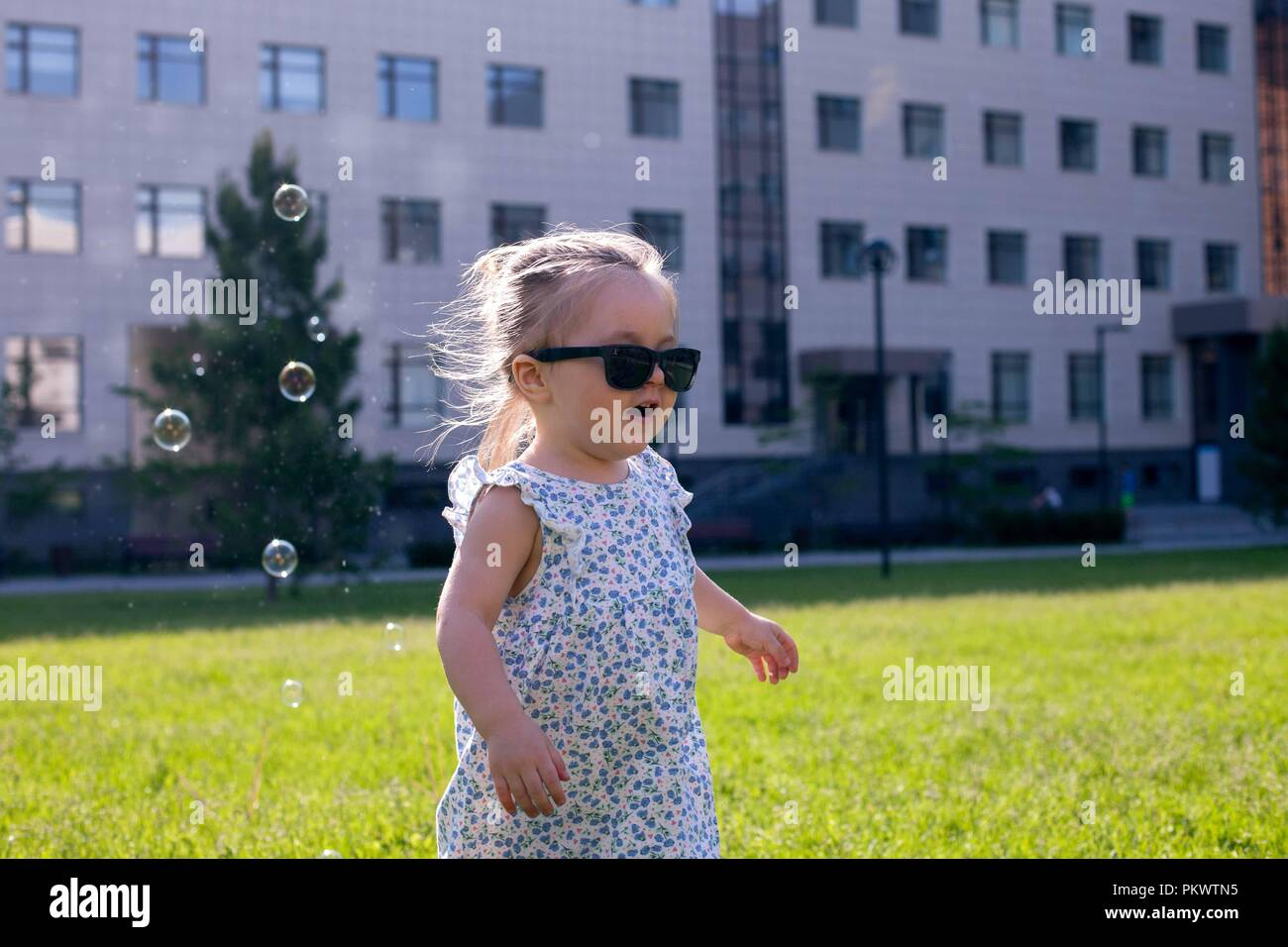 b31cdf8d5300eb Vue sur un mignon petit bébé fille en lunettes de soleil dans le parc de la