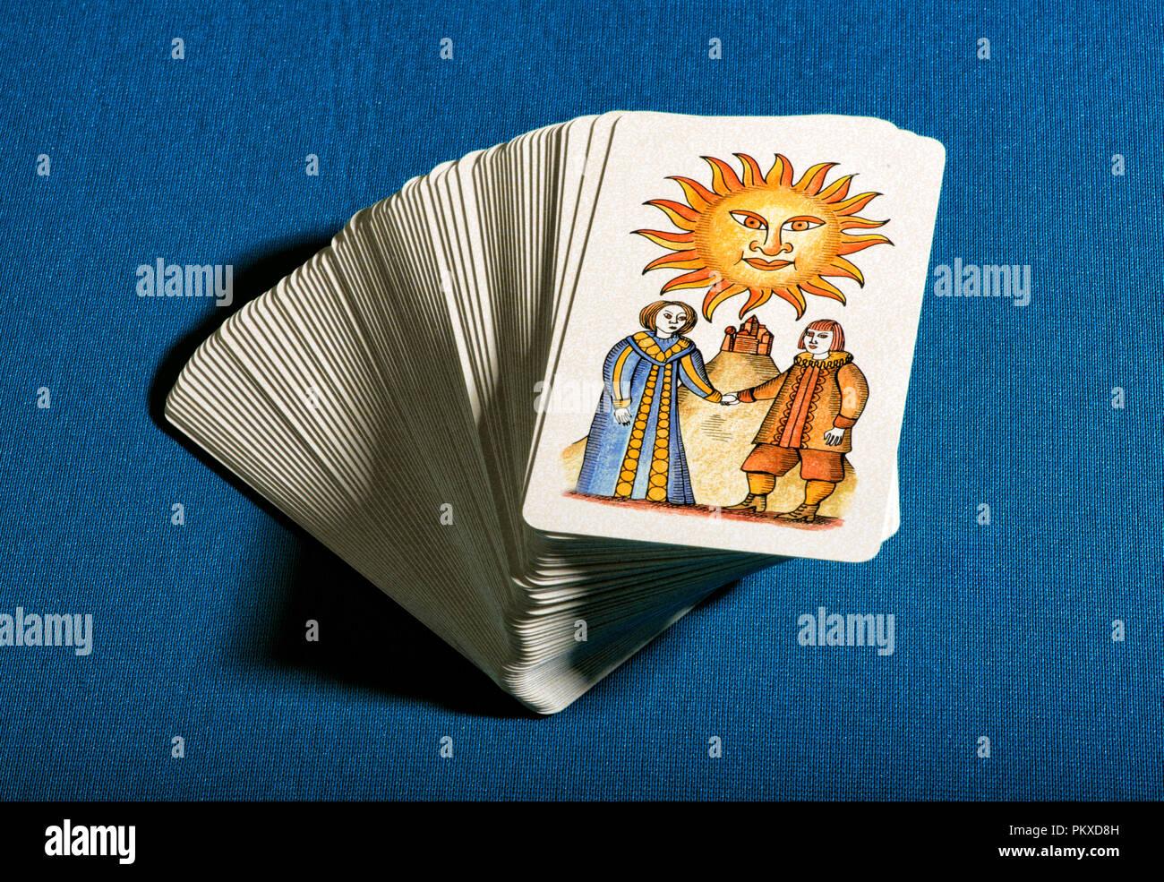 Jeu de cartes de tarot empilé avec la carte graphique montrant le soleil au-dessus de la bonne fortune conceptuelle et d'optimisme sur fond bleu Photo Stock