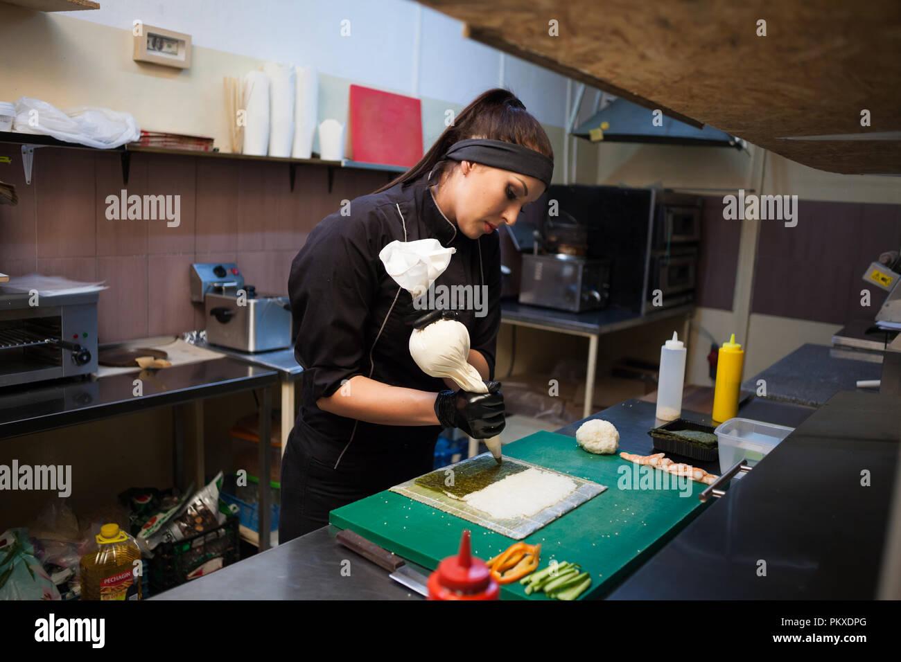 Femme cuisinier prépare des sushis sur une cuisine de restaurant Photo Stock