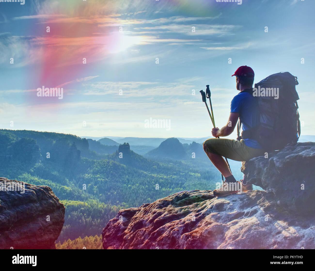 Homme assis sur le rocher en montagne et regarder le lever du soleil sur le paysage. Composition de la nature. Photo Stock