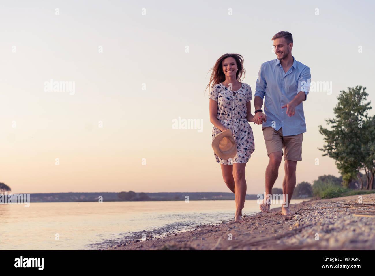 Couple en train de marcher sur la plage au coucher du soleil Photo Stock