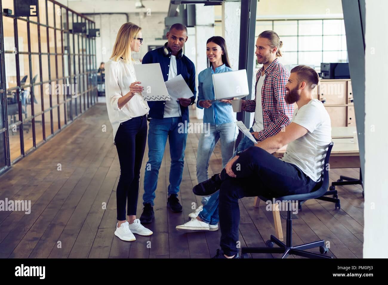Travailler en équipe. Longueur totale de jeunes gens modernes dans smart casual wear planning business stratégie alors que jeune femme pointant sur grand papier dans le couloir. bureau Photo Stock
