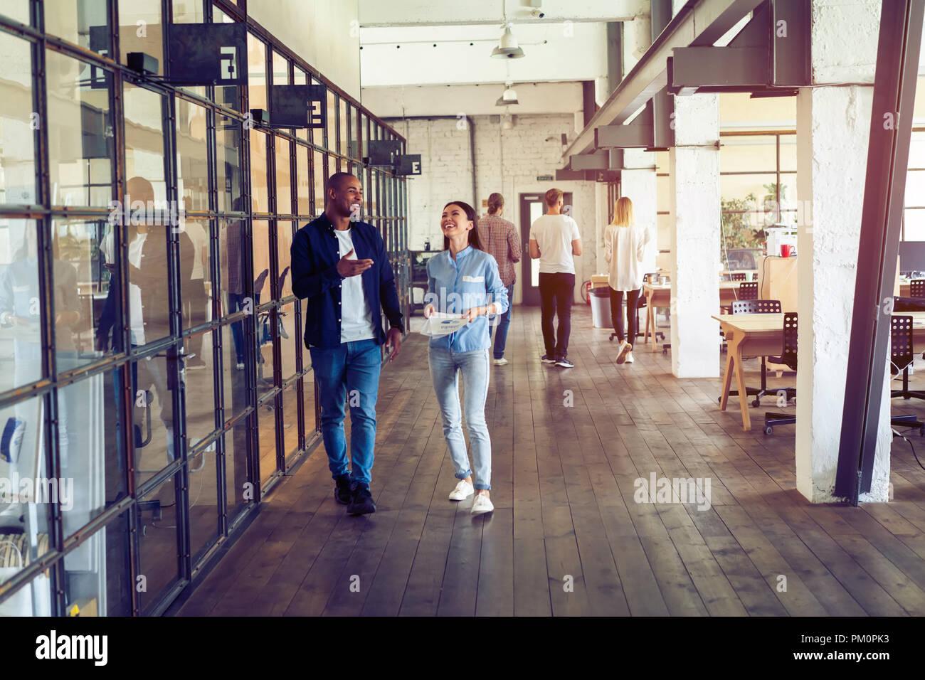 Rattrapage avant la réunion. Longueur totale de jeunes gens modernes dans smart casual wear discuter affaires et souriant tout en marchant à travers le corridor. Photo Stock