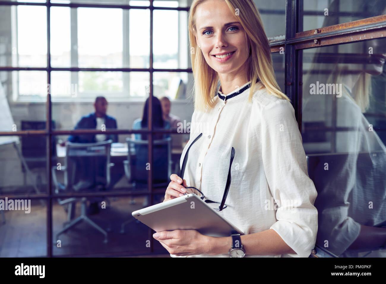 Ce qui conduit son équipe au succès. Certain young woman holding digital tablet and looking at camera avec sourire tandis que ses collègues travaillant dans l'arrière-plan. Photo Stock