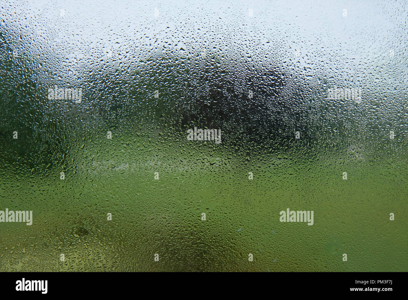 Vue à travers la fenêtre des pluies sur jour morne Photo Stock