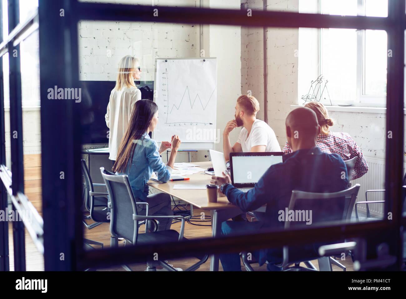 Travailler dur pour gagner. Businesswoman effectuant une présentation d'affaires à l'aide d'un chevalet tout en travaillant dans le bureau de création. Photo Stock