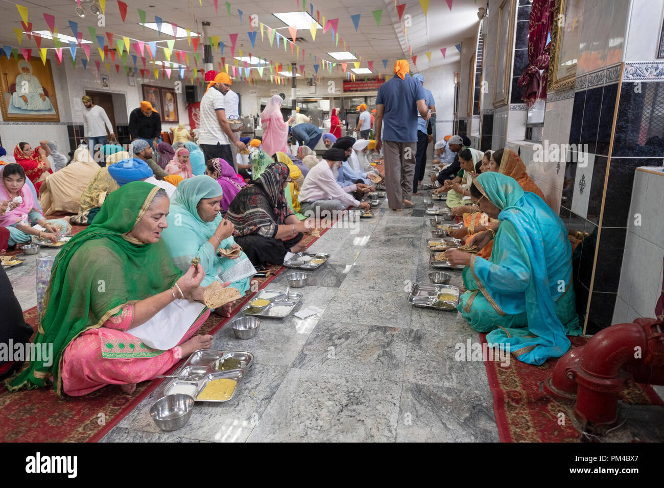 Les femmes et certains hommes de manger dans un temple Sikh langar où un repas végétarien est servi gratuitement à tous sans exception. Photo Stock