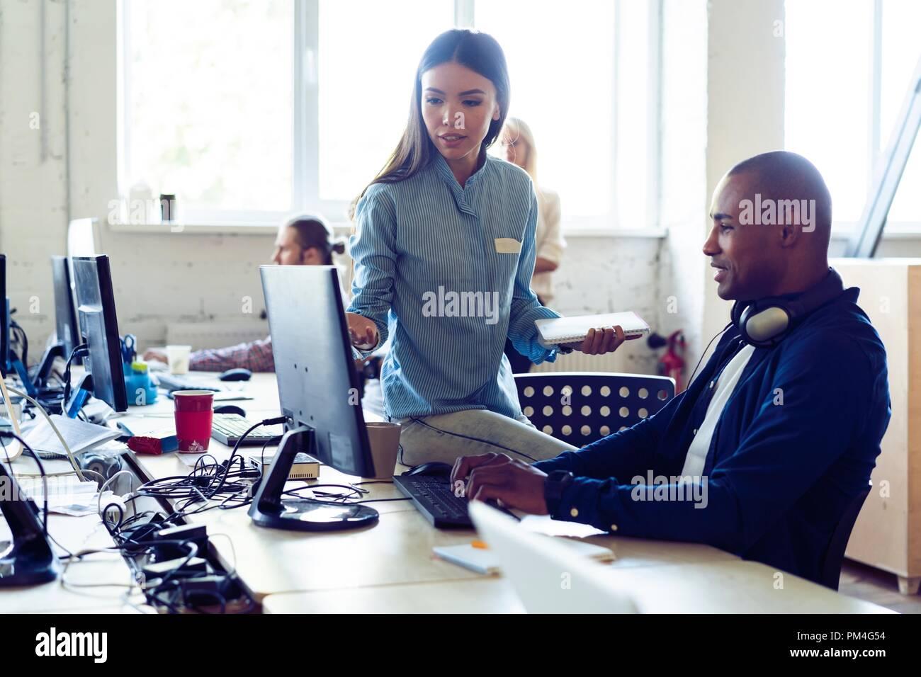 Dure journée de travail. Vue supérieure de jeunes gens modernes dans smart casual wear discuter affaires alors qu'il était assis dans le bureau de création. Photo Stock