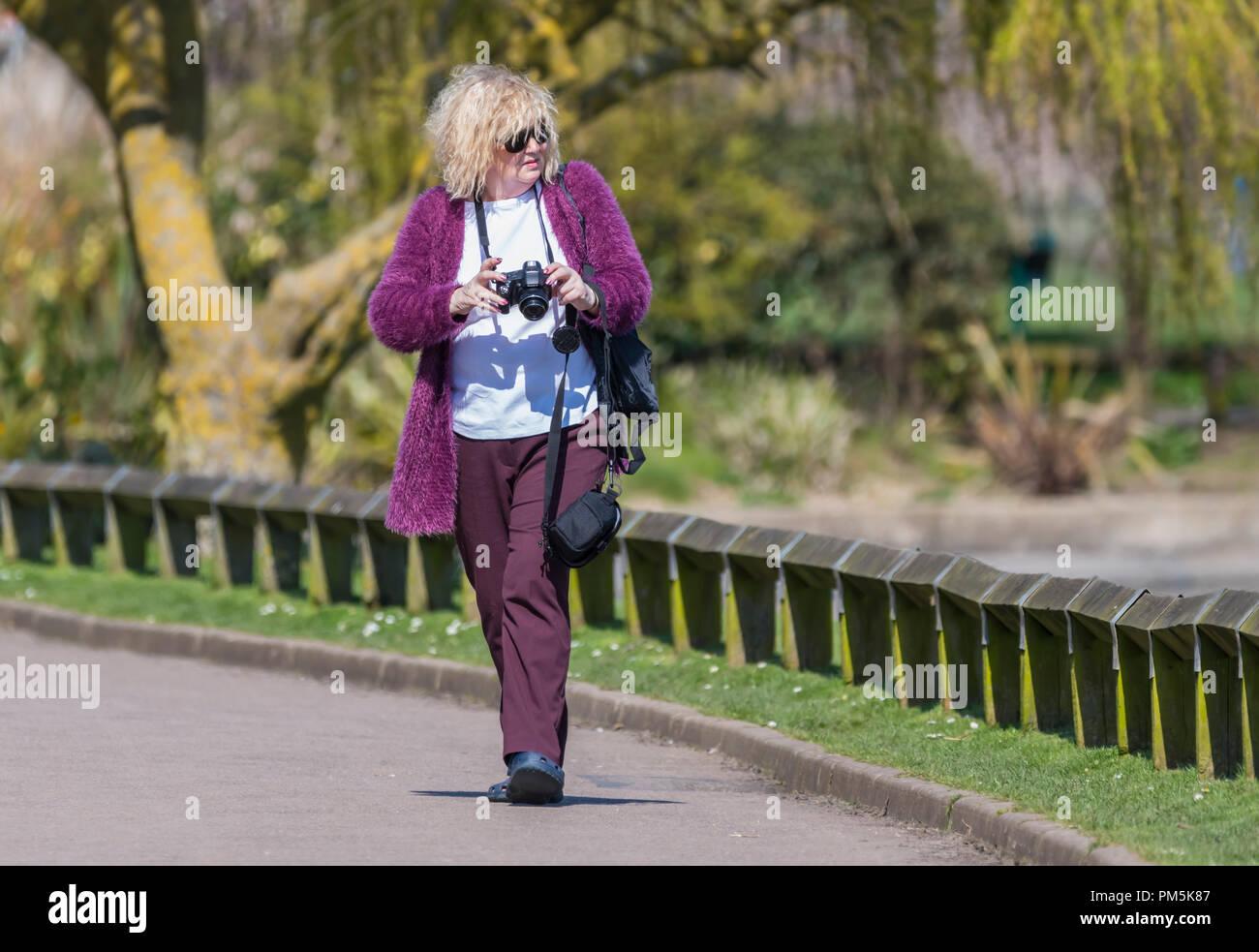 Femme d'âge moyen en se promenant dans un parc avec un appareil photo à la recherche de choses à photographier. Photo Stock