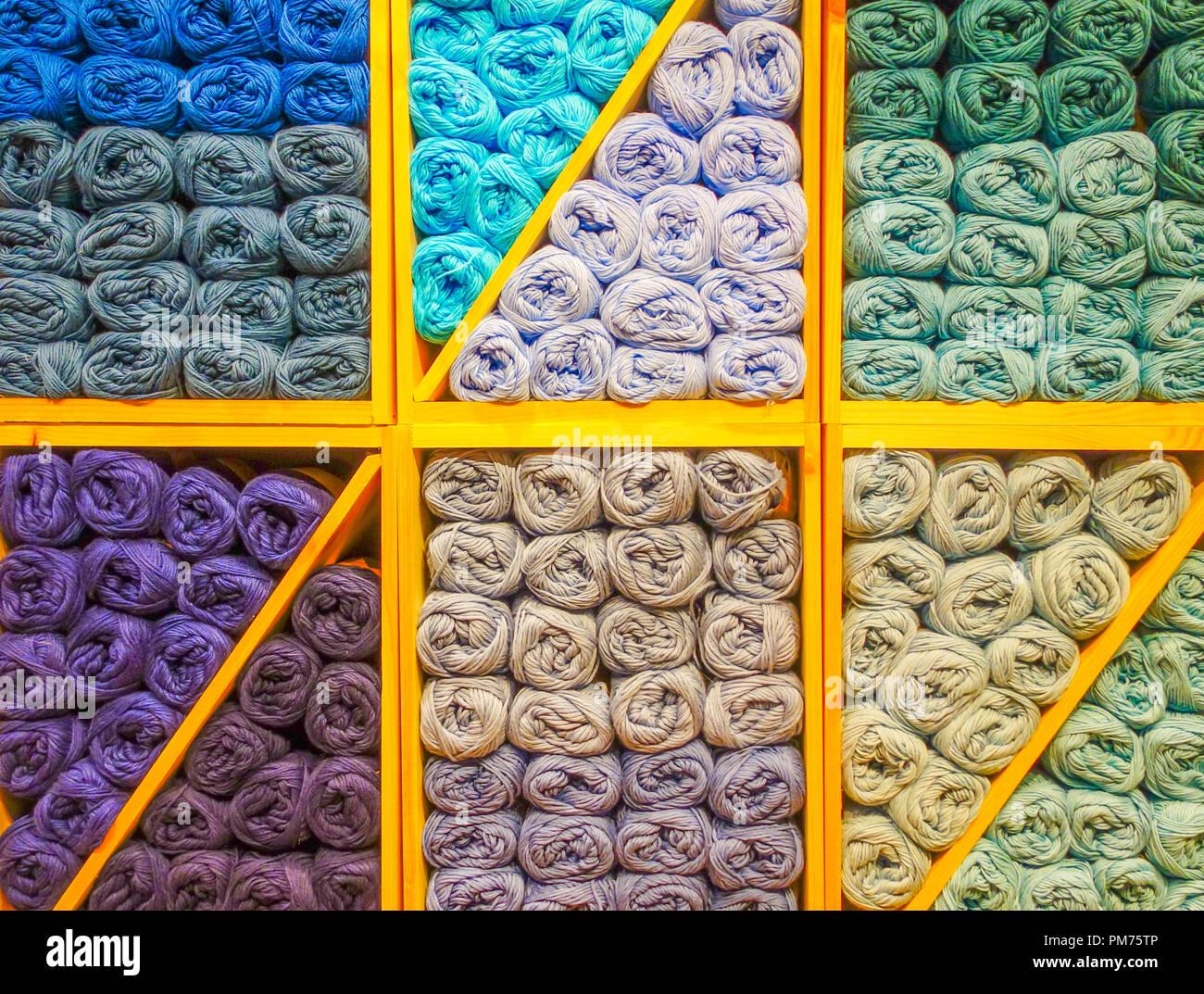 Rouleaux de laine colorés empilés sur des étagères de magasin d