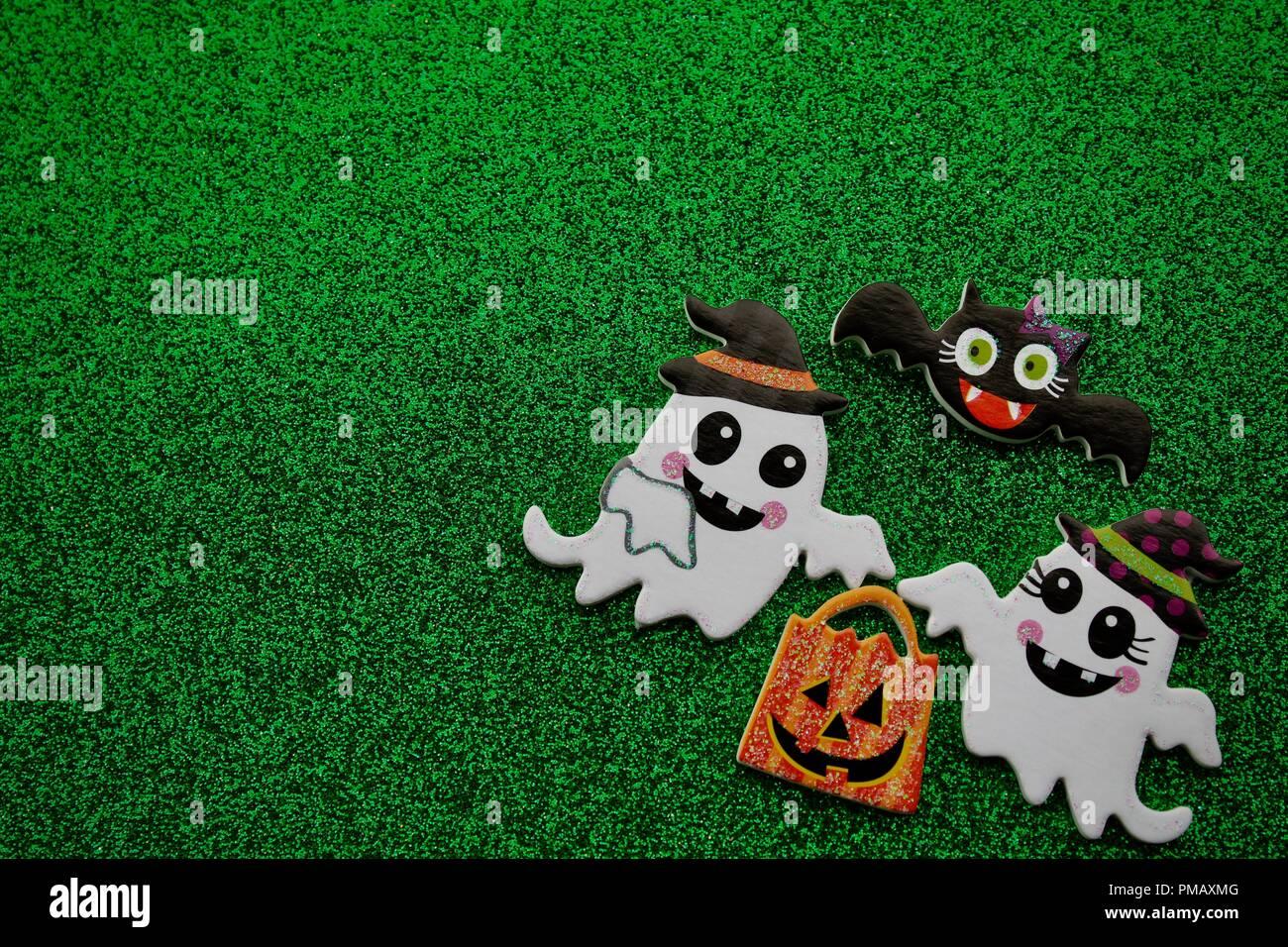 Deux fantômes transportant une citrouille trick or treat sac avec une chauve-souris volant au-dessus des noirs sur fond vert. Photo Stock