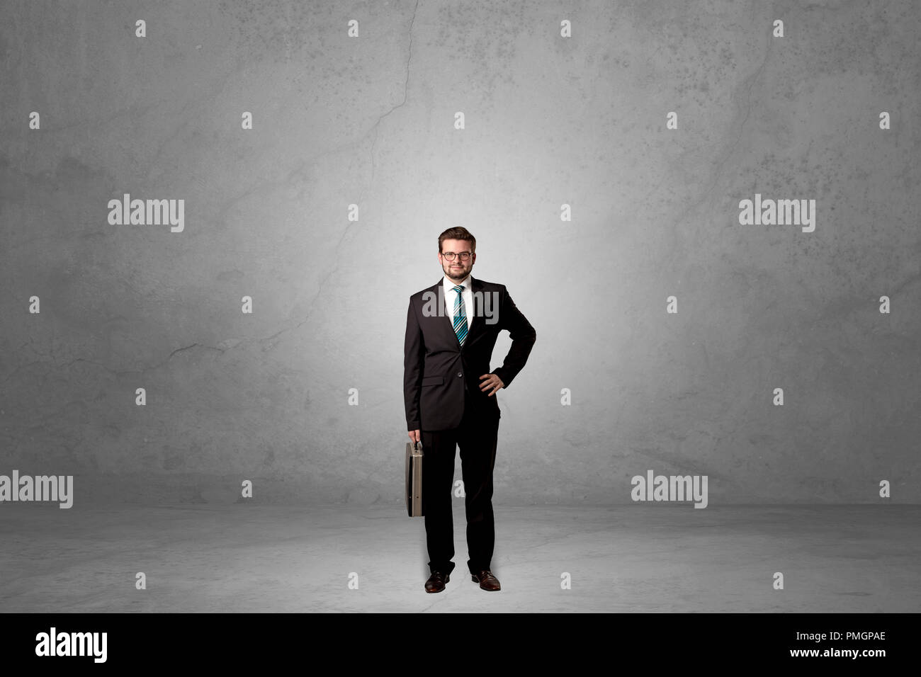Seul handsome businessman standing dans une sombre salle vide Photo Stock