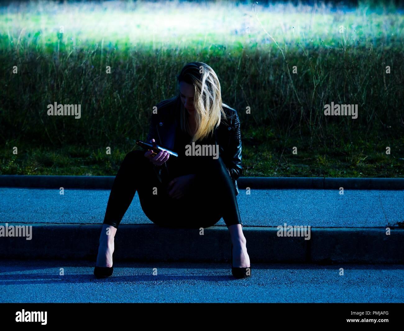 Jeune femme de 20 ans assis sur le bas de la route à la bouteille de bière dans la main tenant l'alcool addict sentiment misérable obscurité nocturne nocturne Photo Stock