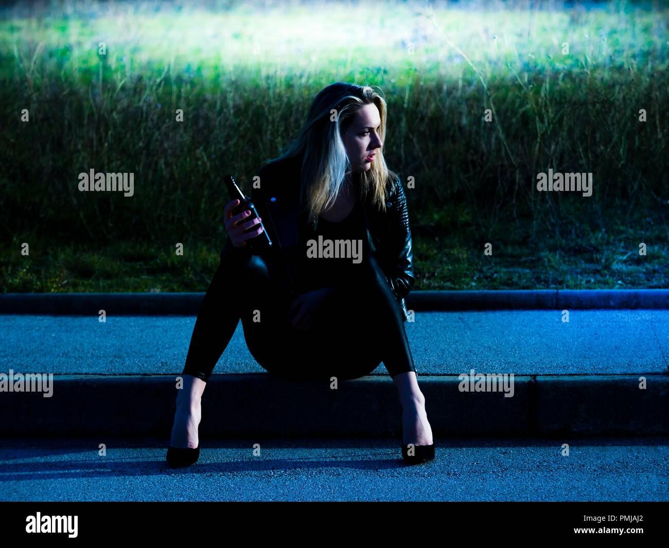 Jeune femme 20s faible assis sur la bouteille de bière dans la main tenant à l'écart de côté en attente de quelqu'un quelque chose de transports Photo Stock