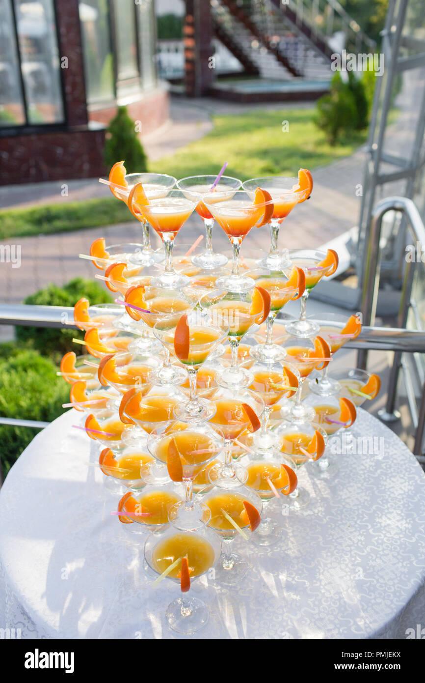 Pyramide de lunettes à la célébration. Des cocktails colorés près. une partie sur le coucher du soleil Photo Stock