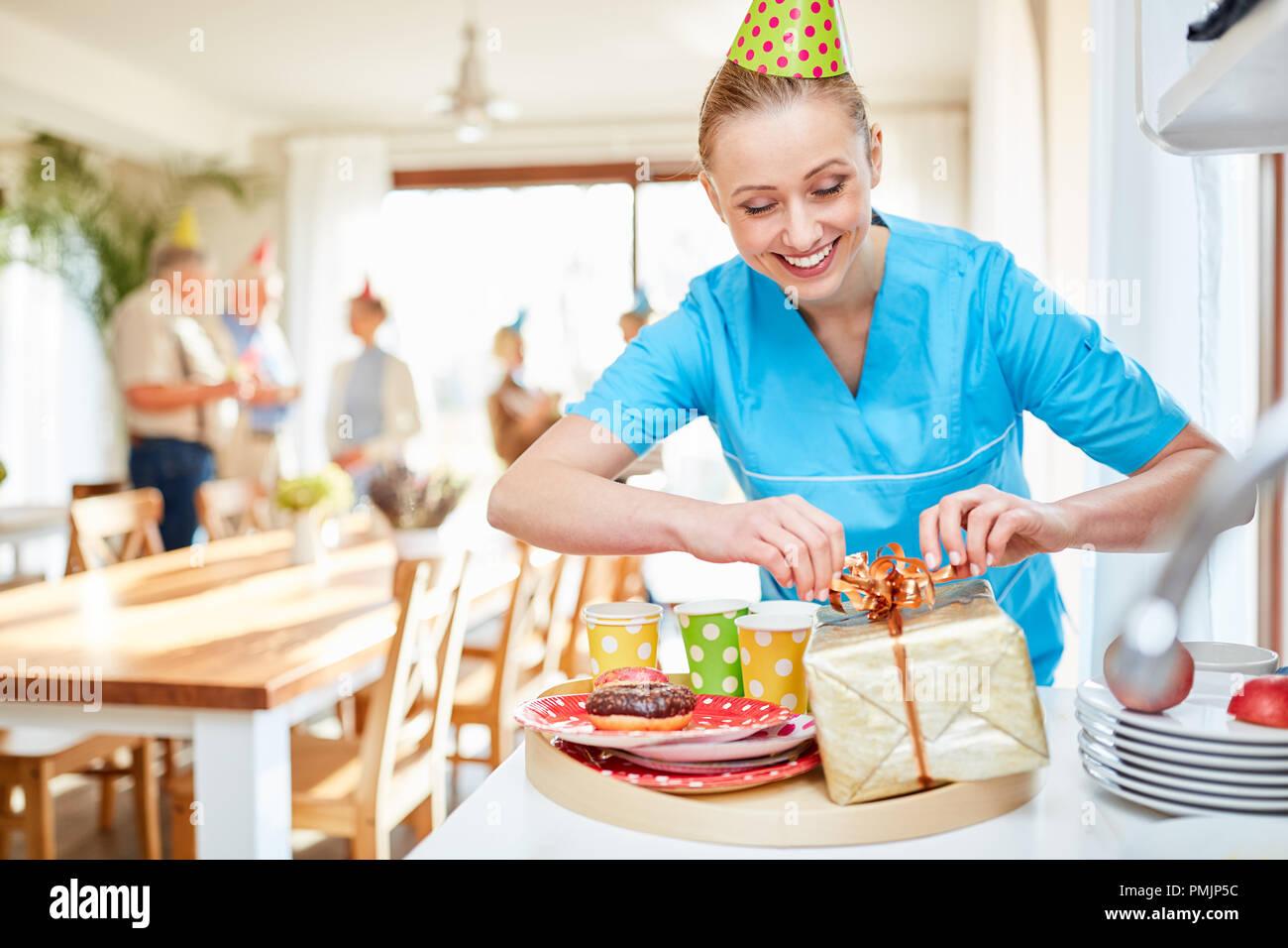 Soignant un sourire packs présents sur un anniversaire à la maison de retraite Photo Stock