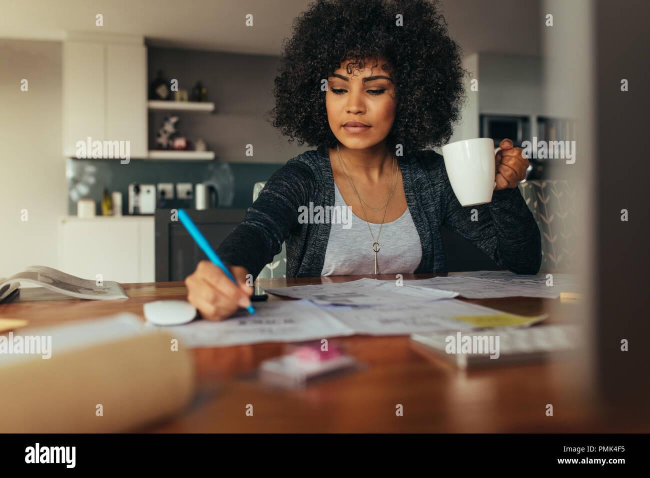 D'femelle plan du projet avec tasse de café dans la main. Architecte d'intérieur de corriger un dessin alors qu'il était assis au bureau à domicile. Photo Stock
