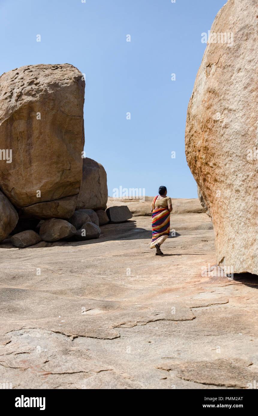 Femme marche à côté d'énormes rochers sur l'Hemakuta Hill donnant une idée de l'échelle à Hampi, Karnataka, Inde Photo Stock