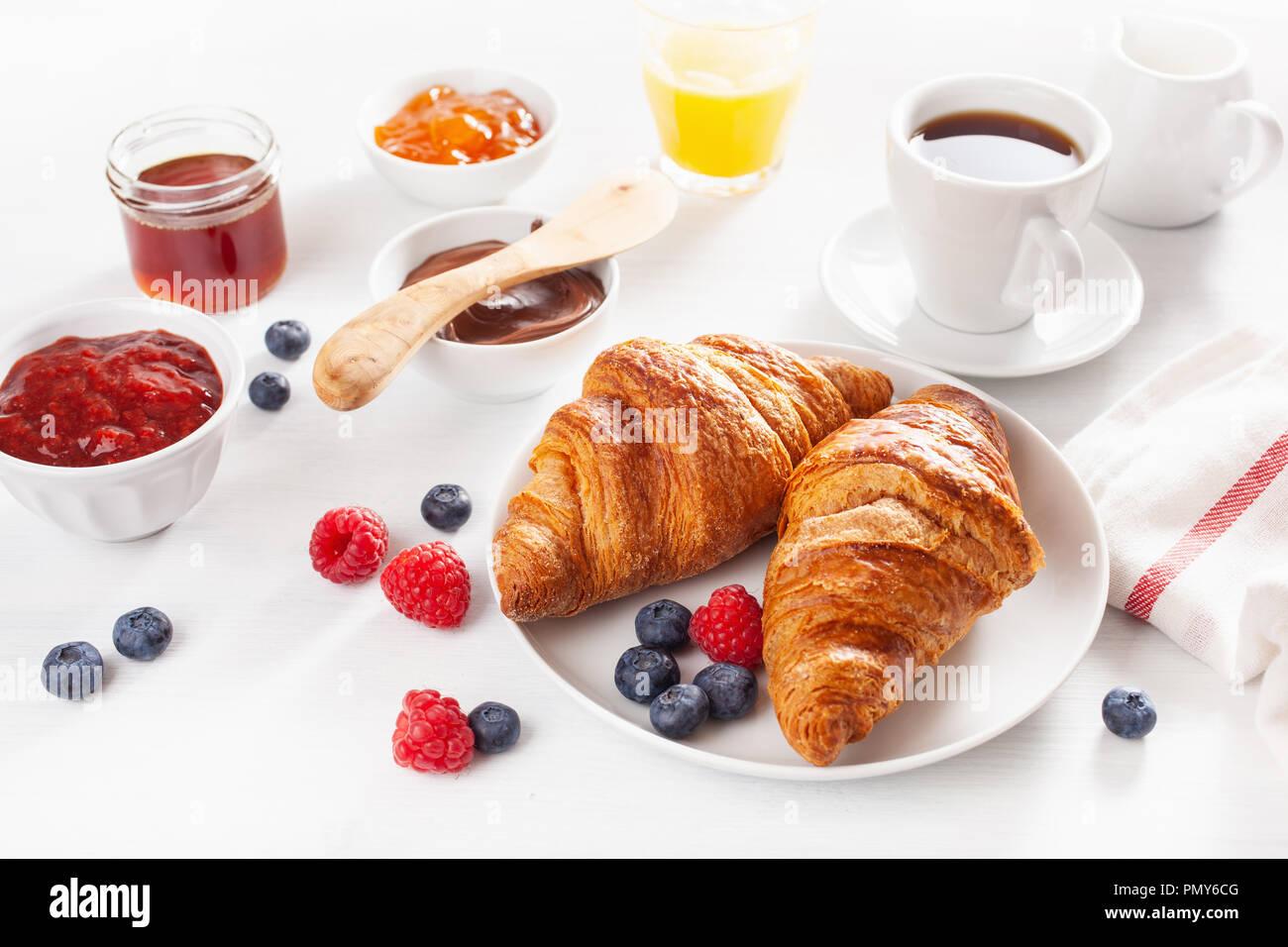 Petit déjeuner avec croissant, confiture, pâte à tartiner au chocolat et café Photo Stock